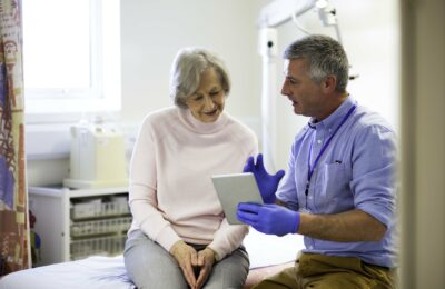 Doctor explaining results in an examination room holding a tablet