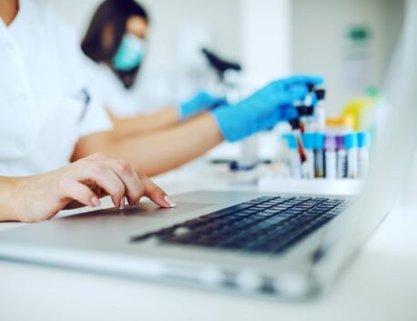 laptop in laboratory and other hand holding test tube with blood sample