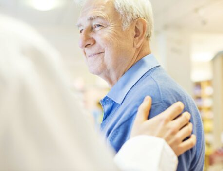 Smiling senior man looking at doctor